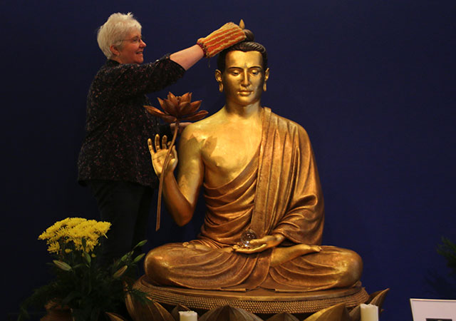 Woman cleaning Buddha statue